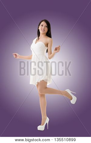 Smiling Asian young woman, full length portrait isolated.