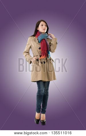 Attractive Asian lady with coat in winter, full length portrait isolated .