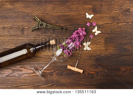 Bottle of wine wineglass with lilacs and decorations on the wooden background