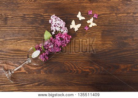 Wineglass with lilacs and butterfly decorations on the wooden background