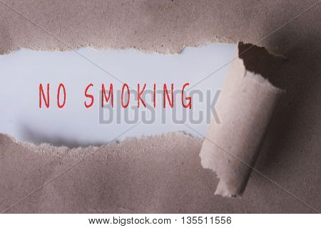 torn paper with NO SMOKING word. Copyspace area.