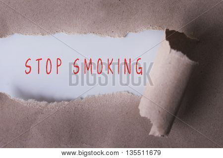 torn paper with STOP SMOKING word. Copyspace area.