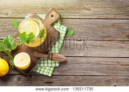 Lemonade pitcher with lemon, mint and ice on garden table. Top view with copy space