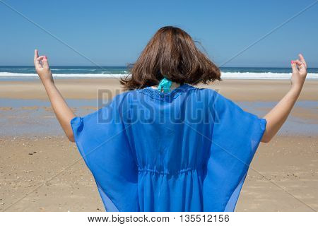 Beautiful Positive Brunette Girl Clothing In Blue Standing At The Seaside On The Rock And Meditating