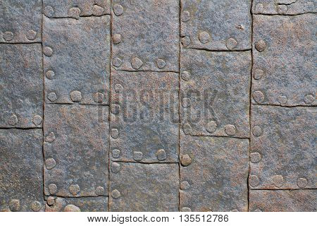 Sheet of ancient military armor with rivets. Texture background
