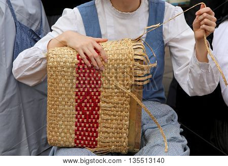 Young Girl With Tapering Fingers Of The Hand Creates A Straw Bag