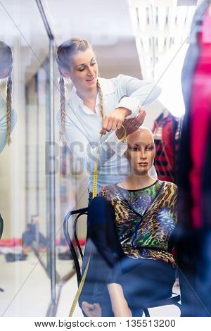 Window dresser working at shop promotion putting new fashion collection on mannequin