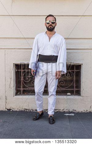 MILAN ITALY - JUNE 20: Fashionable man poses outside Etro fashion show building during Milan Men's Fashion Week on JUNE 20 2016 in Milan.