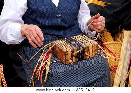 Wrinkled Hands Of An Elderly Woman While Twist The Straw To Crea