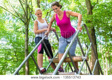 Two women, one pregnant, at fitness sport in climbing park