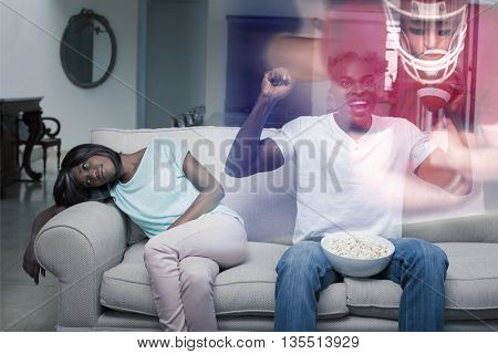 Composite image of man watching sport on television next to his bored wife at home