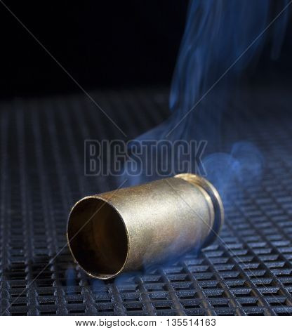 Handgun shell after being fired with smoke rising