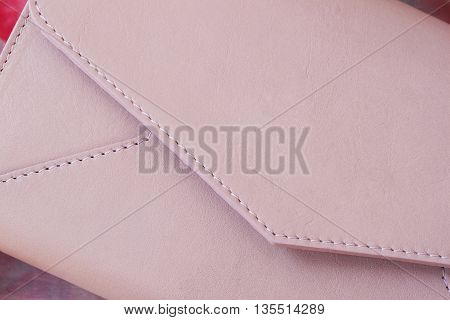 Close-up pink clutch in form of an envelope with space for your logo or text