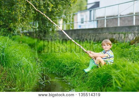 Happy little kid boy fishing on a river with selfmade fishing rod  on sunny summer day. Happy child having fun. Active leisure for children outdoors.