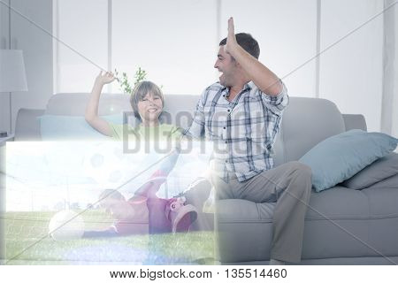 Composite image of father and son giving high-five in front of soccer match on television at home