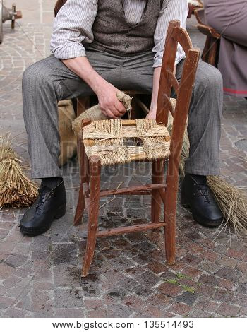 Senior Artisan Mender Of Chairs With Woven Straw Shelters A Chai
