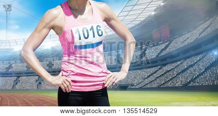 Portrait of sportswoman chest is posing with hands on hips against view of a stadium