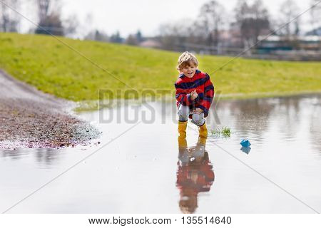 Happy little kid boy in rain boots playing with paper ship by a puddle on warm spring day. Active leisure for children. Child having fun outdoors.