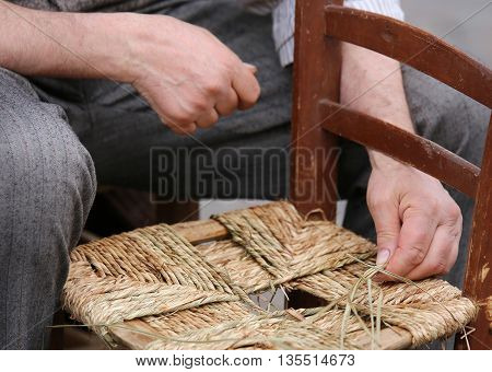 Hands Of A Craftsman While Reparing The Chair Of Straw