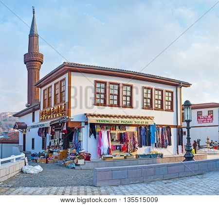 ANKARA TURKEY - JANUARY 16 2015: The scenic cottage of the modern neighborhood in old town with the wooden minaret on the background on January 16 in Ankara.