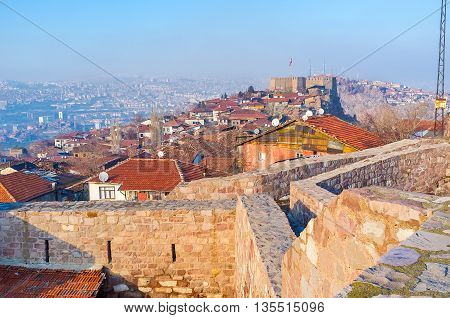 The red tiled roofs of the old houses between the buildings of the medieval Hisar Citadel Ankara Turkey.