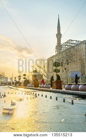 ANKARA TURKEY - JANUARY 16 2015: The frozen pond with the bright sun path on ice and the huge wall of the ancient Augustus Temple on the background on January 16 in Ankara.