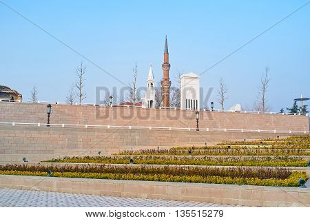 The scenic flower beds with the stone mihrab minbar and the minaret of Haci Bayram Mosque on the background Ankara Turkey.