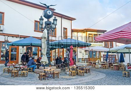 ANKARA TURKEY - JANUARY 16 2015: The cozy outdoor teahouse in the city center where locals like to spend their time drinking tea coffee and smoking on January 16 in Ankara.