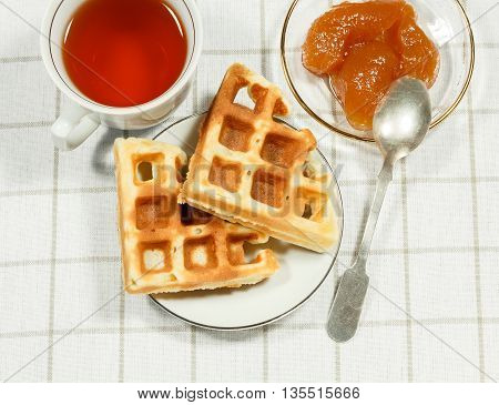 Belgian waffles on white plate and cup of black tea with apple jam. Serving on the light-colored tablecloths.