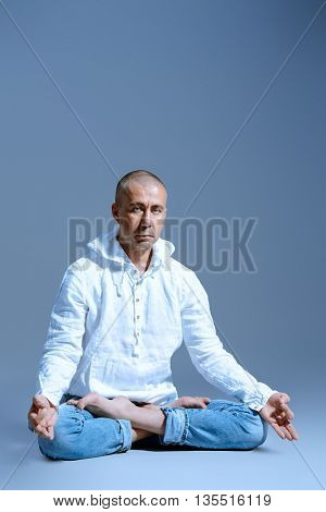 Experienced yoga master performs different poses and exercises. Lotus pose. Studio shot.