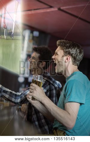 Composite image of friends are watching sport match on television in a pub