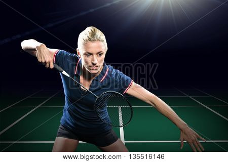 Badminton player playing badminton against view of a badminton field