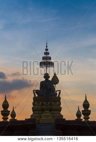 Buddha statue and monk was teaching Novice at sunset in Saraburi