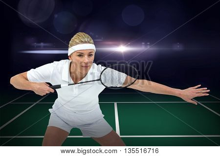 Composite image of female athlete holding a badminton racket ready to serve on badminton field