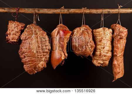 Traditional sausages hanging on a black background
