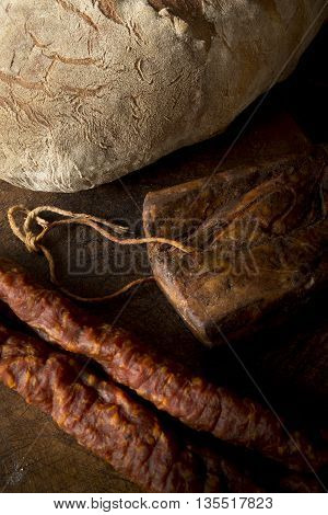 Rustic bread and meat on vintage wooden cutting board