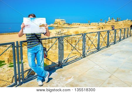 CAESARIA ISRAEL - MAY 19 2016: The tourist explores the map of the archaeological site standing among the ancient ruins on May 19 in Caesaria.