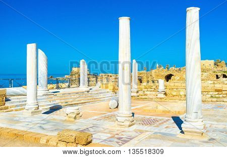 The marble columns and the colorful stone mosaic on the floor of the ruined ancient temple of Caesaria Israel.