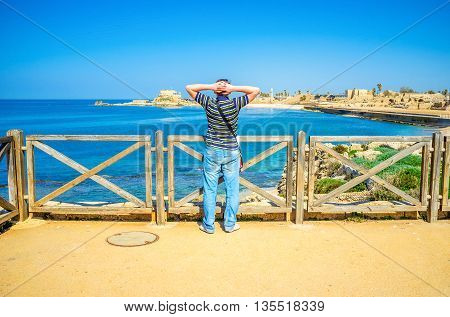 CAESARIA ISRAEL - MAY 19 2016: The young tourist watches the coast of Caesaria ful of the ancient Roman ruins and picturesque places on May 19 in Caesaria.