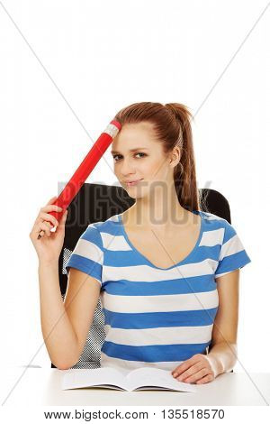 Pretty teenager woman holding huge pencil.