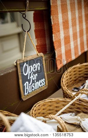 Open for business slate board sign at a vintage looking shop