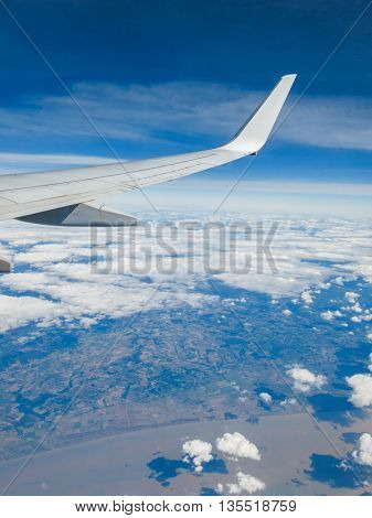 Wing of a commercial airplane flying above a coastal region.