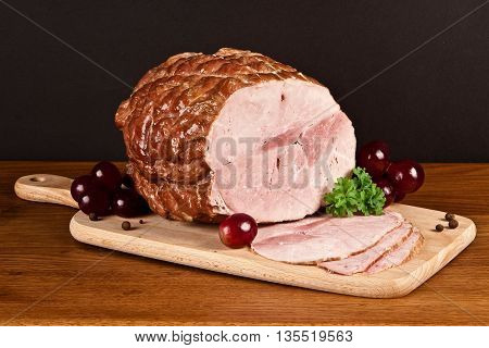 smoked ham with slices, on a woden board, with grapes