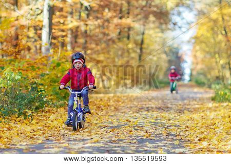 Two little kids boys, best friends in autumn forest with bikes. Active siblings, children with bicycles.