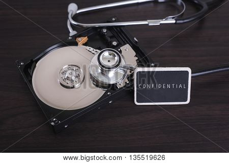 A stethoscope scanning for lost information on a hard drive disc with CONFIDENTIAL word on board