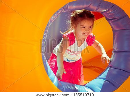 Smiling girl in the playground . child on a colorful trampoline