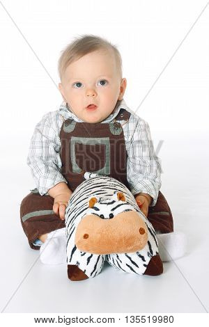 cute baby boy in brown jumpsuite sitting in the full-lenght and holding a toy cow of pillows, white background, isolated