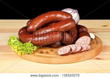 composition of smoked sausage on a woden board, with onion,  garlic and lettuce