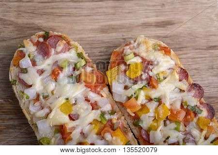 baked baguette with salami, cheese and vegetable