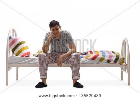 Depressed young man sitting on a bed and contemplating isolated on white background